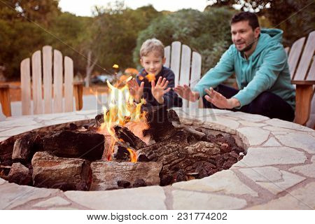 view of firepit and happy smiling family of two, father and son, warming their hands by the fire and enjoying time together in the background stock photo