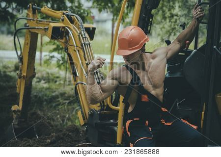 Sexy man with nude torso near construction equipment or excavator on background. Sexy builder concept. Handsome man or bodybuilder wears overalls. Muscular builder in hard hat shows biceps, poses. stock photo