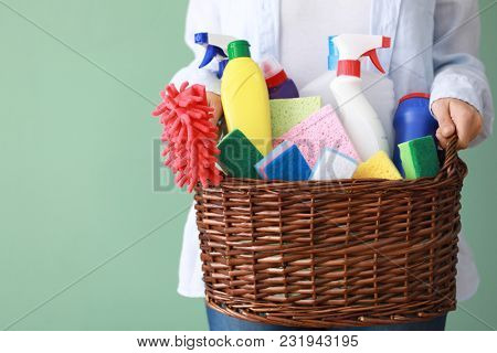 Woman holding basket with cleaning supplies on grey background stock photo