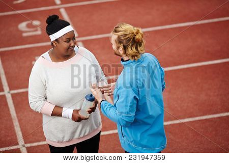 Young plump female listening to her instructor speaking about progress in sport stock photo