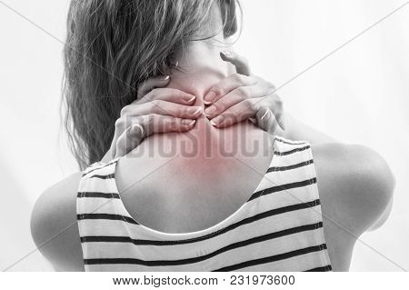 Woman With Upper Back And Neck Pain Standing With Her Back To The Camera And Her Hand Rubbing Her Sh