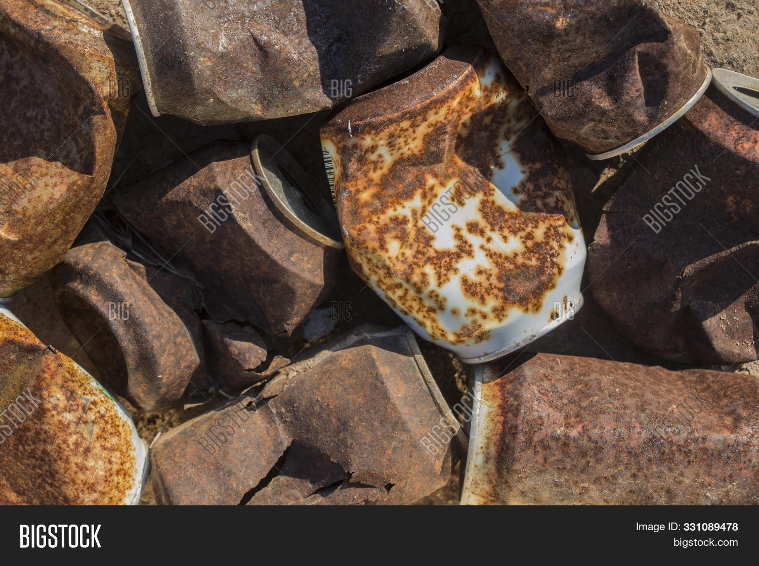 close-up of overhead view of rusty tin cans, texture of beverage cans, rusty cans of soda, rusty cans lying in the field, trash