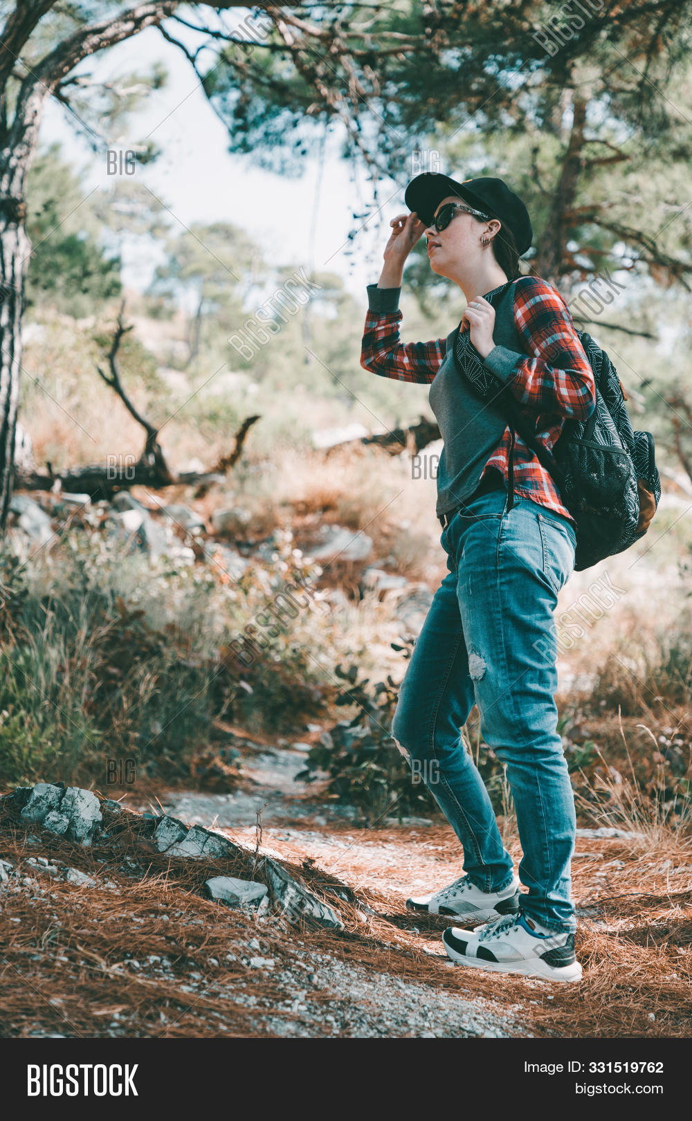 Tourism And Outdoor Activities. A Woman In A Cap And Glasses, With A Backpack On Her Back, Is Lookin