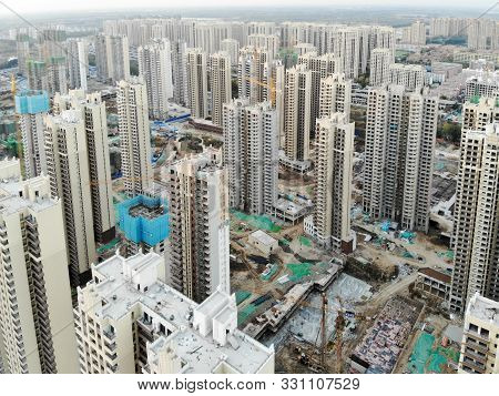 Aerial view of massive building sites in construction with tower crane. Building blocks apartment in construction in developing part of the city of Tianjin in China. Estate construction site. stock photo