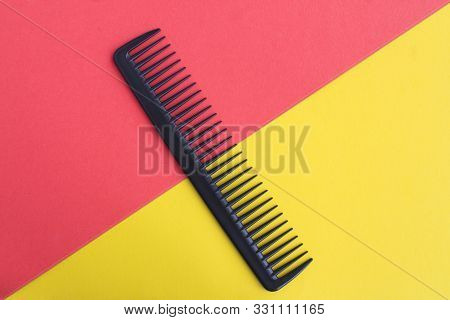 Black hair comb in the center of the bicolor background. Top view. Copy space. stock photo