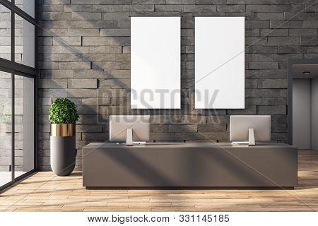 Modern office lobby interior with reception desk, computers, shadows, city view, daylight and empty frame on stone wall. Mock up, 3D Rendering stock photo