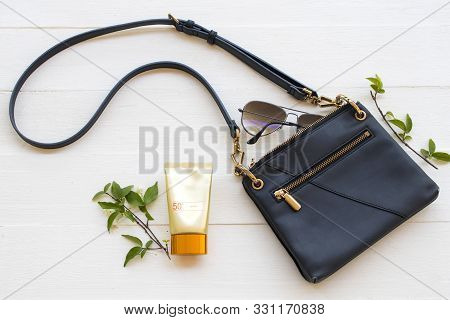 sunscreen spf50 health care for skin face with sunglasses ,shoulder bag accessories of lifestyle woman relax arrangement flat lay style on background white wooden stock photo