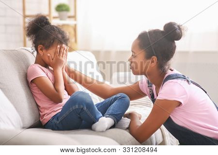 Caring african american teen girl calming her sad crying baby sister, side view stock photo