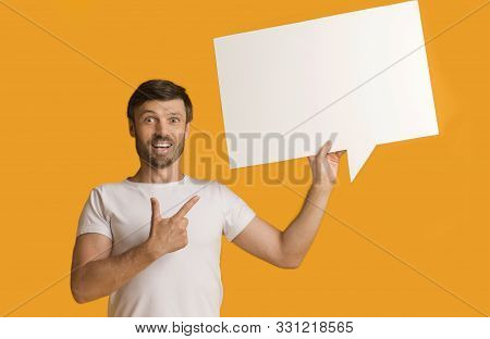 Look Here. Shocked Guy Showing Blank Speech Bubble Pointing Finger Standing Over Yellow Background In Studio. stock photo