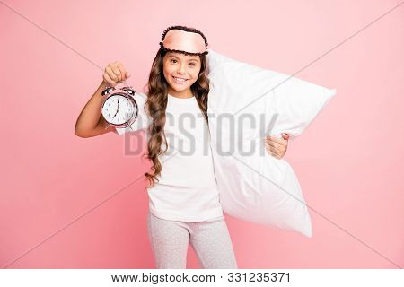 Portrait of her she nice attractive sweet lovely cute cheerful cheery wavy-haired pre-teen girl holding in hands pillow bell clock isolated over pink pastel color background stock photo
