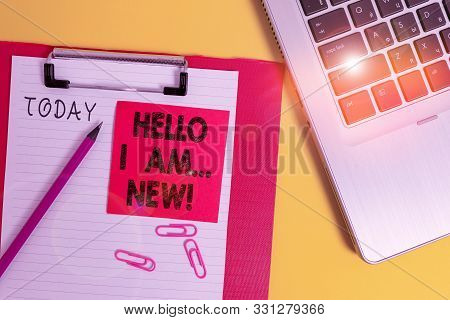 Conceptual hand writing showing Hello I Am New. Business photo text used as greeting or to begin telephone conversation Metallic laptop clipboard paper sheet pencil colored background. stock photo