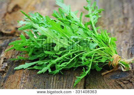 Fresh green arugula leaves on wooden rustic background . Rocket salad or rucola, healthy food, diet. Nutrition concept stock photo