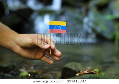 Poor Venezuela in the hands of powerful people. Crooked man holds flag of Venezuela near stream. Concept of dominance and criminality. Prove of depraved and avariciousness. Problems with drogs stock photo