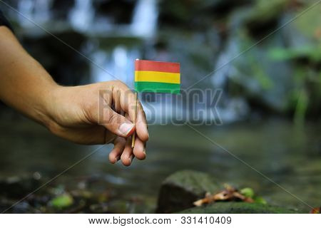 Poor Bolivia in the hands of powerful people. Young man holds flag of Bolivia near stream. Concept of humanity and dominance. Prove of depraved and avariciousness. Problems with drogs. stock photo