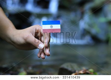 Poor Paraguay in the hands of powerful people. Young man holds flag of Paraguay near stream. Concept of humanity and dominance. Prove of depraved and avariciousness. Colour man waves with flag. stock photo