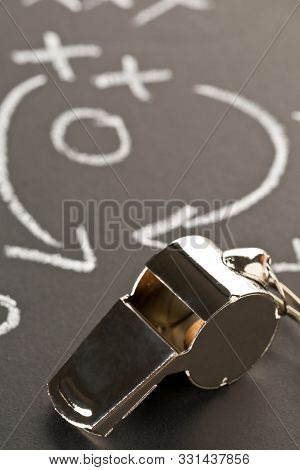 Soccer sports referee chrome whistle on blackboard background with game strategy drawing - selective focus stock photo