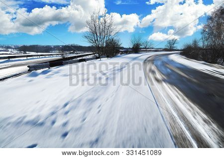 Big blue truck with red trailer on the countryside road with houses against blue sky with clouds stock photo