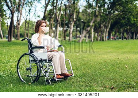 Senior adult elderly asia women sit on wheelchair and reading book outdoor stock photo