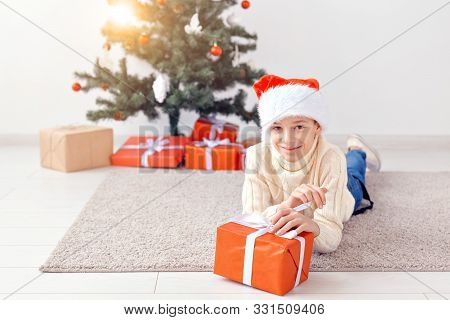 Holidays, christmas, childhood and people concept - smiling happy teen boy in santa hat with gift box over christmas tree background stock photo
