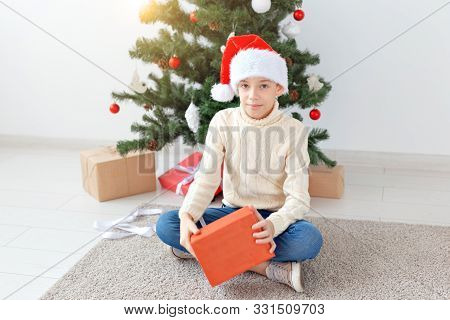 Holidays, christmas, childhood and people concept - smiling happy teen boy in santa hat opens gift box over christmas tree background stock photo