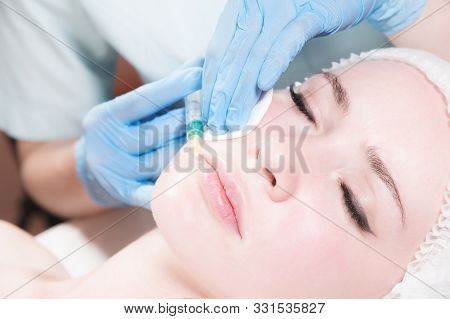 Close-up Attractive young woman gets anti-aging face injections. She lies calmly in a clinic or salon. An experienced young cosmetologist fills female wrinkles with hyaluronic acid from a syringe stock photo