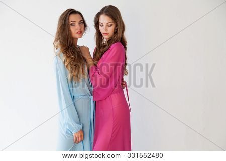 Two beautiful fashionable women in lingerie in the bedroom on the bed stock photo