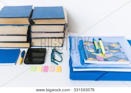 Back to school background. Stationery accessories - notebooks, plastic folder, pens, stickers, glasses with smartphone and stack of books education concept . stock photo