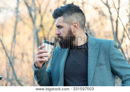 Time for myself. Hipster hold paper coffee cup. Relaxing coffee break. Businessman bearded guy drink coffee outdoors. Drink it on the go. Man thoughtful bearded hipster prefer coffee take away. stock photo