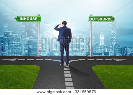 Businessman at crossroads deciding between outsourcing and inhou stock photo