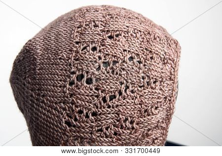 Baby bonet taupe knit isolated on light background, baby accessory infant hat with detailed lace stitches of crafted yarn. stock photo