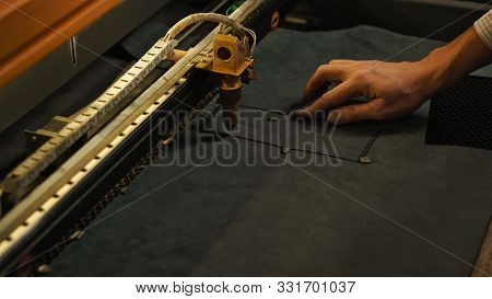 Laser cutting beam artificial leather High precision. Modern machine industrial technology of artificial leather cutting. CNC laser. Masterclass, workshop session stock photo