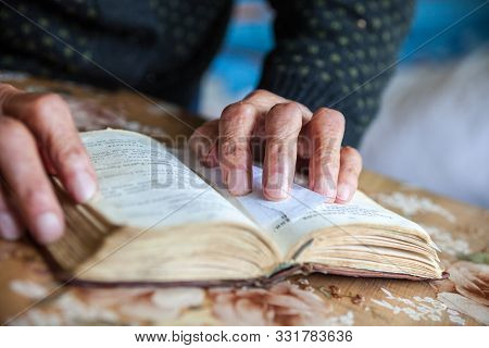 Old woman hands on the open prayer book (Christian prayer book in Ukrainian). Reading the book. Praying. stock photo