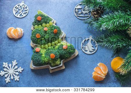 Creative Edible Christmas Tree Of Fresh Broccoli Next To Christmas Tree And Tangerines.concept: Vega