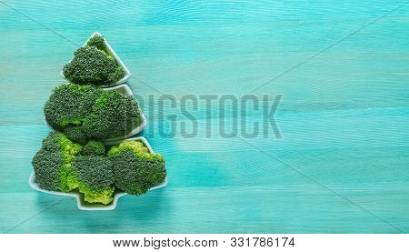 Creative Edible Christmas Tree Of Fresh Broccolion On On Mint Wooden Background.vegan Holiday Ideas.