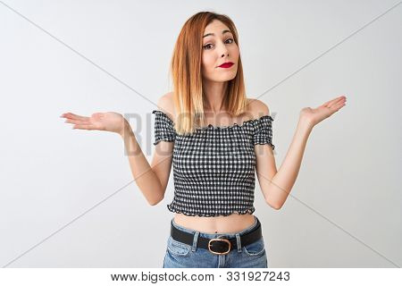 Beautiful redhead woman wearing casual t-shirt standing over isolated white background clueless and confused expression with arms and hands raised. Doubt concept. stock photo