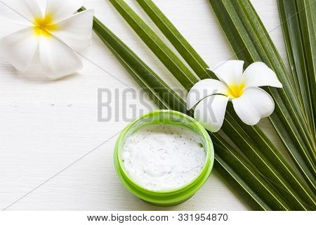 natural herbal coconut scrub health care for surface skin face with coconut leaf ,flowers frangipani arrangement flat lay style on background white stock photo