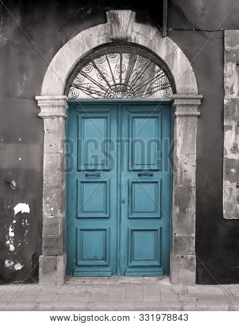 old blue door in an arched stone frame with flaking back painted walls stock photo