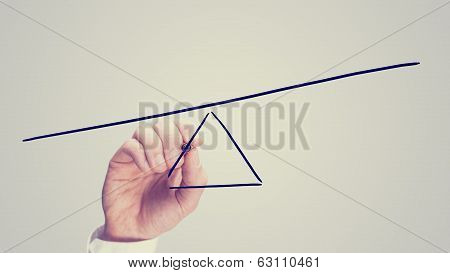 Male hand drawing a seesaw showing an imbalance with one end lower than the other. ** Note: Shallow depth of field stock photo