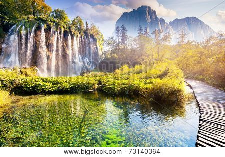 Majestic view on waterfall with turquoise water and sunny beams in the Plitvice Lakes National Park.