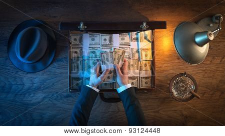 Vintage rich businessman's desk with a briefcase filled with dollar packs he is counting paper currency stock photo