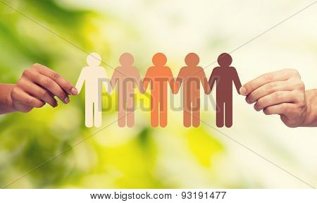 community, unity, people and support concept - couple hands holding paper chain multiracial people over green background stock photo