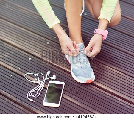 Active runner girl with smartphone and and headphones, tying running shoes laces. Healthy lifestyle,