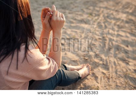 bootless woman sitting on beach at sunset; barefoot female on sand; stock photo