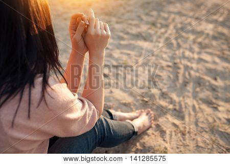 barefoot female sitting on sand in rays of sun; bootless woman on beach at sunset; stock photo