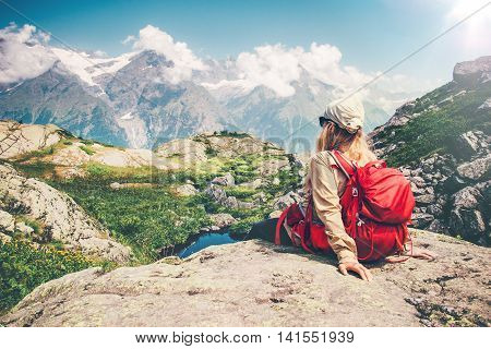 Woman Traveler with backpack relaxing on cliff with mountains landscape on background Travel Lifestyle concept hiking adventure summer vacations