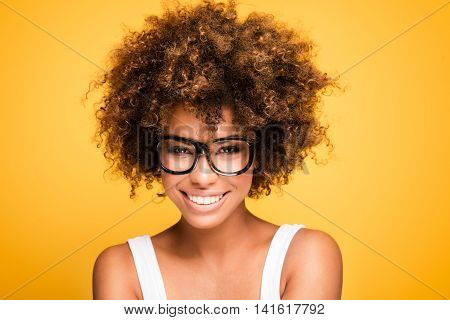 Young beautiful african american girl with an afro hairstyle. Laughing girl wearing eyeglasses. Portrait. Yellow background. Girl looking at camera. stock photo
