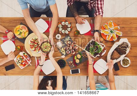 People eat healthy meals at festive table served for party. Friends celebrate with organic food on wooden table top view. Woman pass dish plate to man