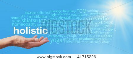 Holistic Therapy Blue Sky Word Cloud -  Female  hand held palm up the word HOLISTIC in white above surrounded by a relevant word cloud on a wide blue sky and bright sunburst background stock photo