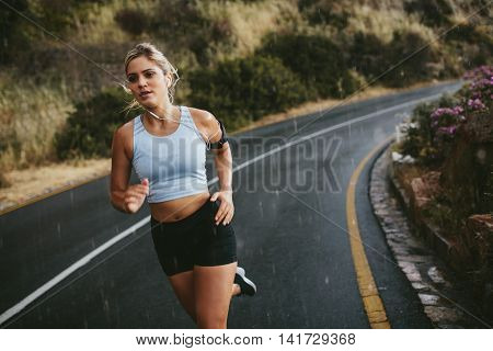 Fit young woman jogging outdoors on highway. Female athlete training running on a rainy day. stock photo