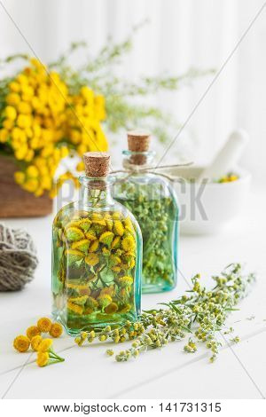 Tincture bottles of tansy and tarragon healthy herbs healing herbs in wooden box and in mortar. Herbal medicine. stock photo